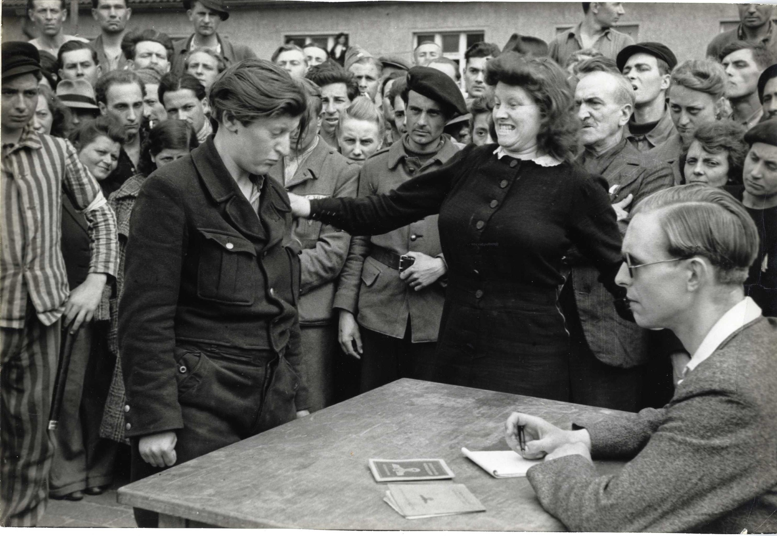 A refugee recognizes her Gestapo informant in a displaced persons camp,  Dessau, Germany, 1945